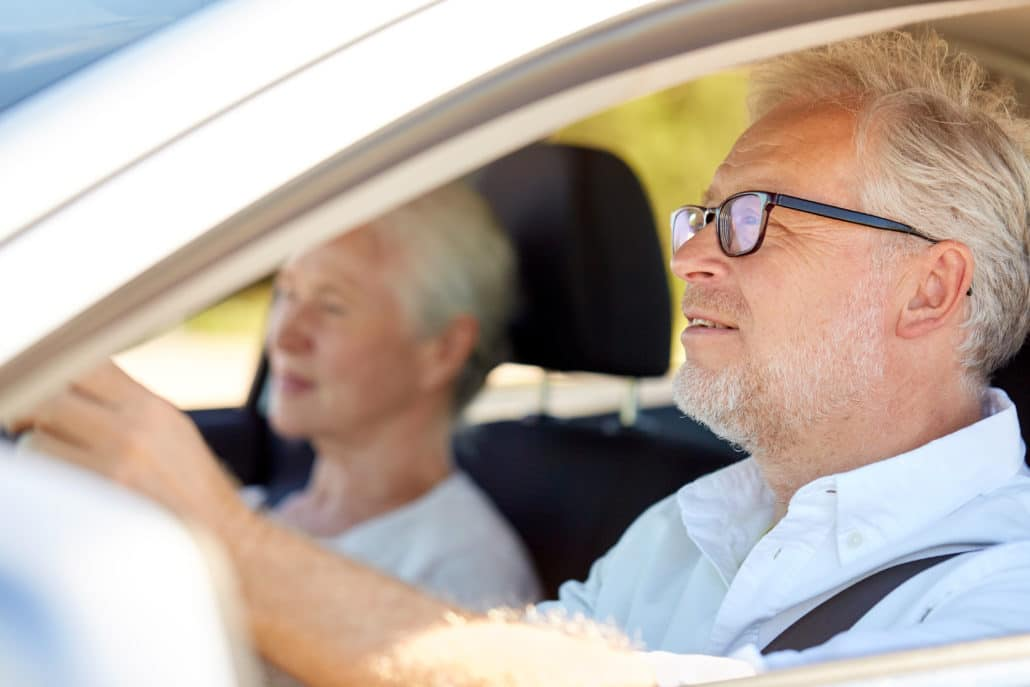 Man och kvinna sitter framtill i bil och blickar framåt