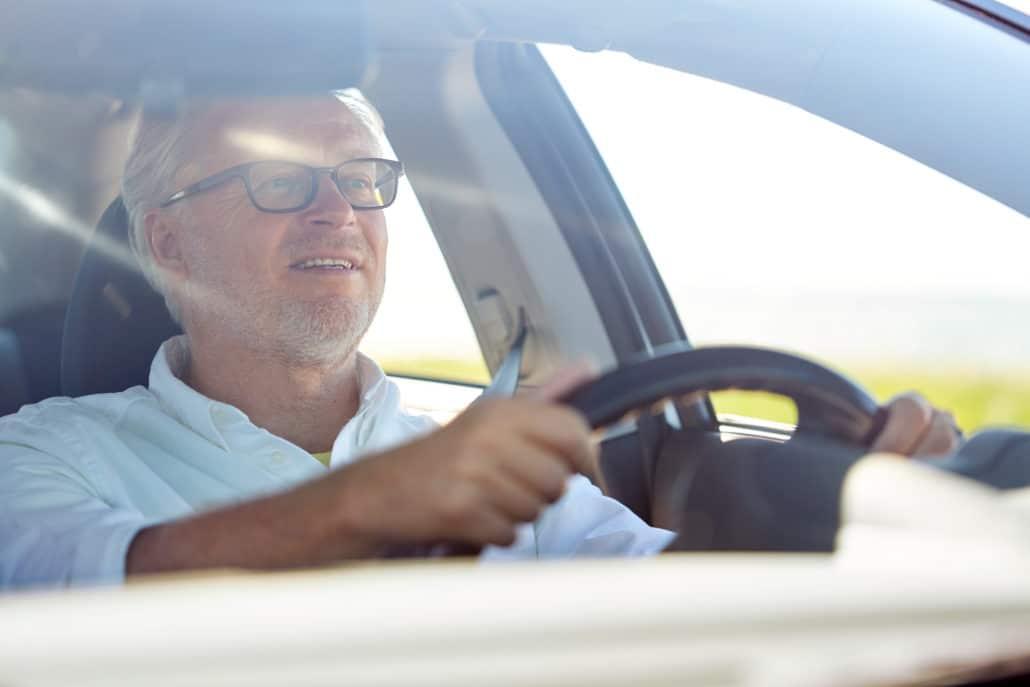 Glad man som kör bil i soligt väder