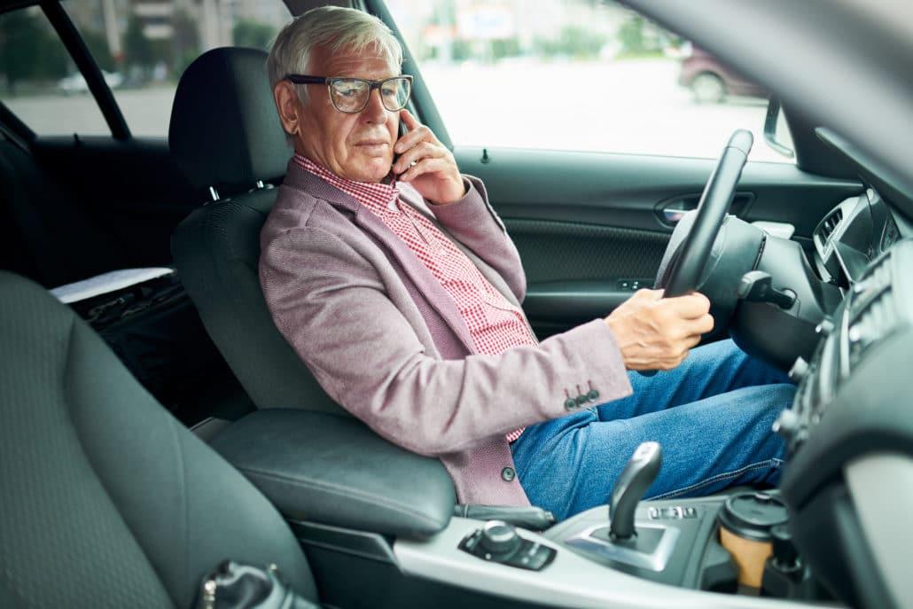 Man sitter i förarsätet i en bil och pratar i mobiltelefon